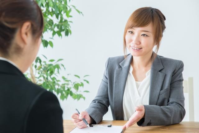 カウンターで契約をする女性の写真画像