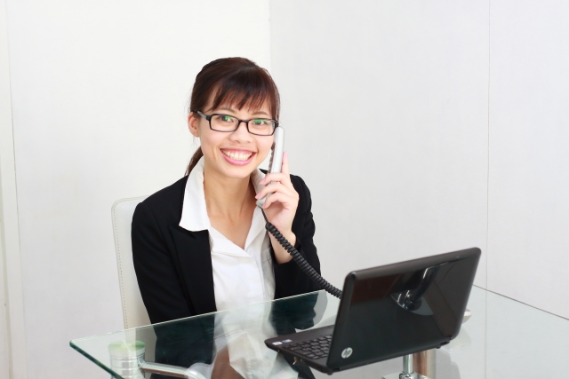 電話・パソコンで応対する女性:写真画像