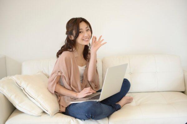 ソファでノートパソコンを見る女性の写真画像