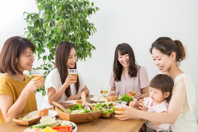 子供と食事パーティーをする女性たちの写真画像